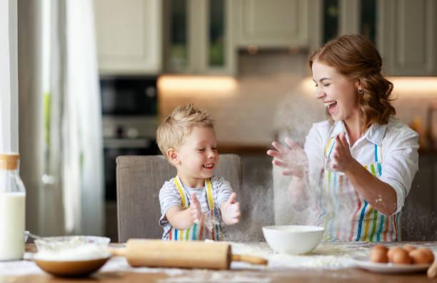 glückliche Familie in der Küche. Mutter und Kind bereiten Teig, backen Kekse – Foto