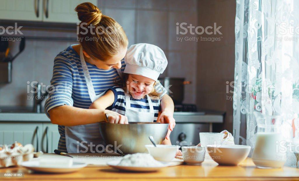 幸福的家庭,在廚房裡。母親和孩子準備麵團,烤餅乾, - 免版稅一個小孩的家庭圖庫照片