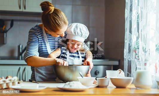 istock happy family in kitchen. mother and child preparing dough, bake cookies 658018162