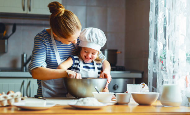 happy family in kitchen. mother and child preparing dough, bake cookies - kids cooking stock photos and pictures
