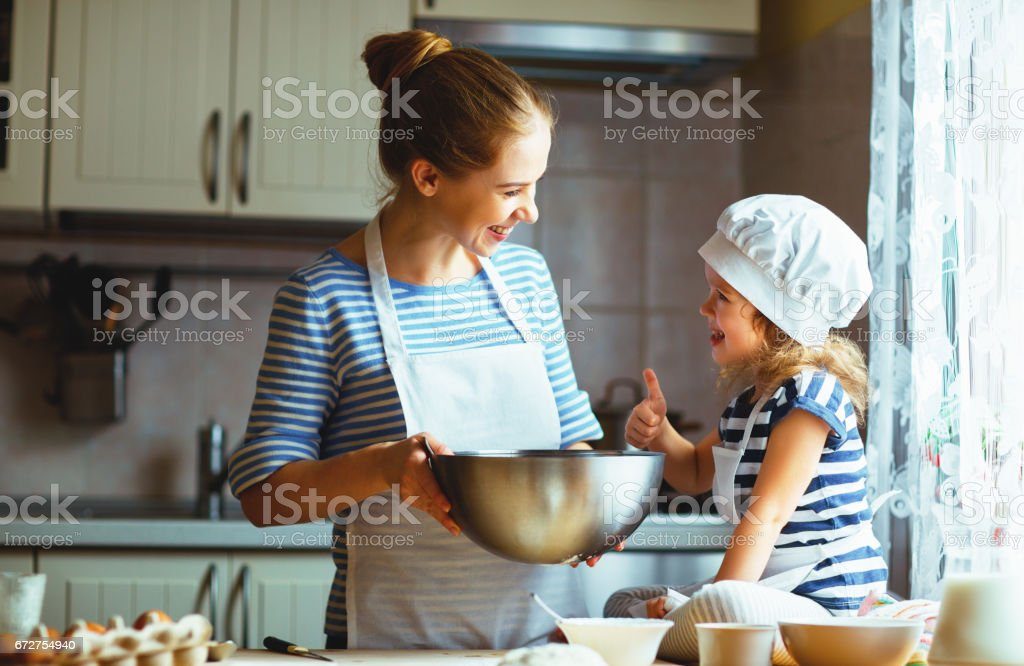 happy family in kitchen. mother and child preparing dough, bake cookies stock photo