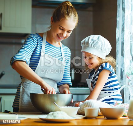 istock happy family in kitchen. mother and child preparing dough, bake cookies 673165876