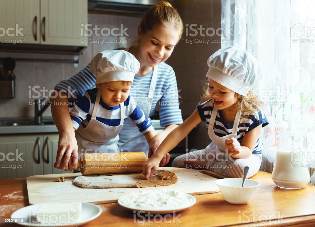 happy family in kitchen. mother and children preparing dough, bake cookies stock photo