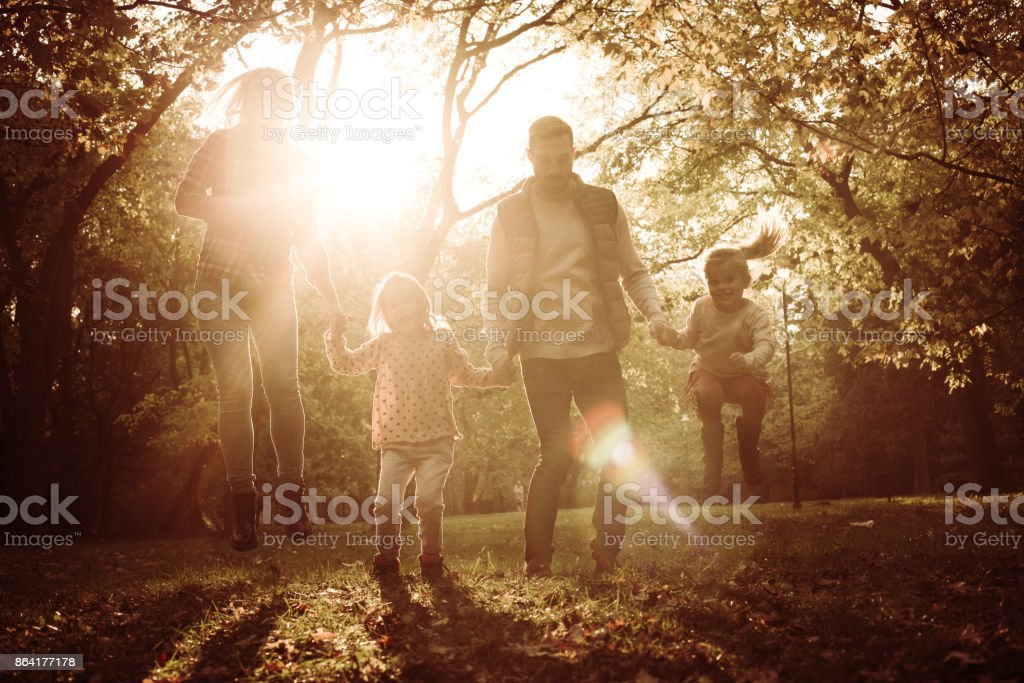Happy family in park jumping trough park and holding hands. royalty-free stock photo