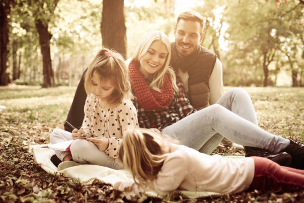 happy family in park together and little girls coloring book. - fall coloring pages stock photos and pictures