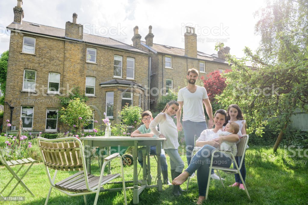 Happy Family In Sunny Back Garden With Suburban Family Home In ...