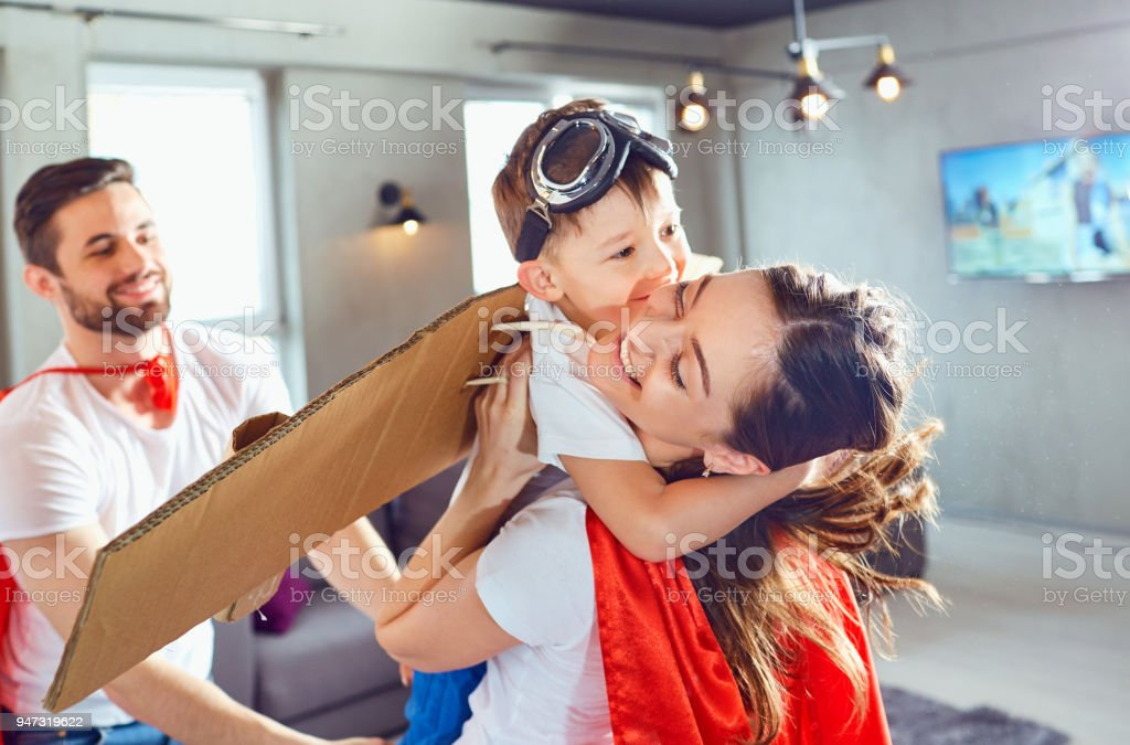 Happy family in superhero costumes playing stock photo