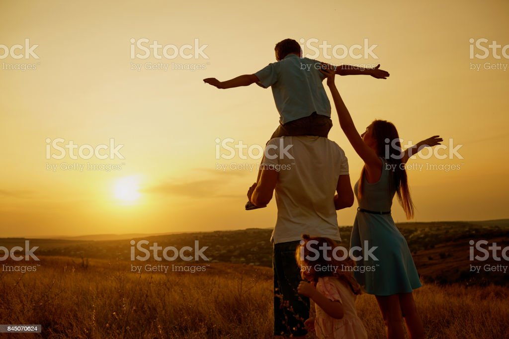 Happy family in the field at sunset. stock photo
