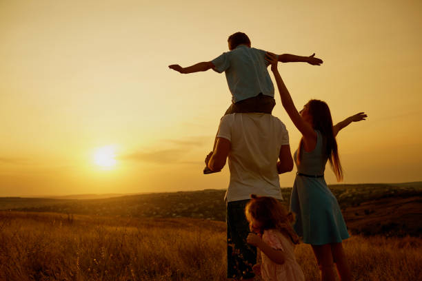 happy family in the field at sunset. - moldova stock pictures, royalty-free photos & images