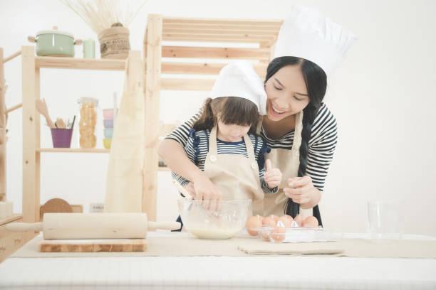 Glückliche Familie in der Küche. Asiatische Mutter und ihre Tochter den Teig vorbereiten, um einen Kuchen zu backen – Foto