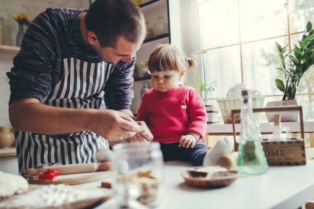 Happy family in the kitchen. Father and daughter are preparing the christmas cookies. stock photo
