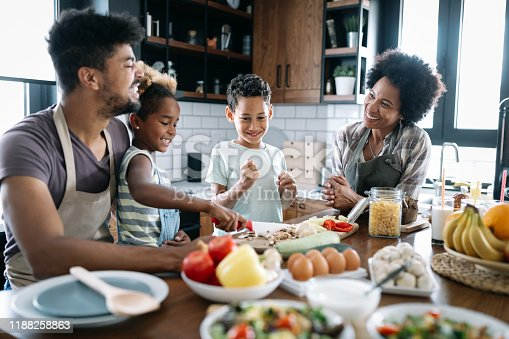 Healthy food at home. Happy black family in the kitchen having fun and cooking together