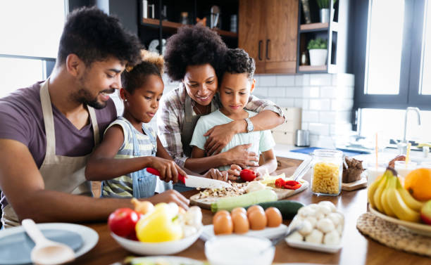 Happy family in the kitchen having fun and cooking together. Healthy food at home. stock photo
