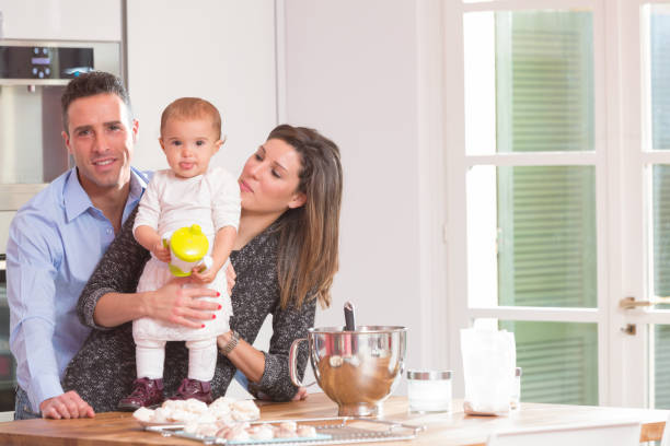 happy family in the kitchen Mom, dad and baby in the kitchen preparing sweets famiglia stock pictures, royalty-free photos & images