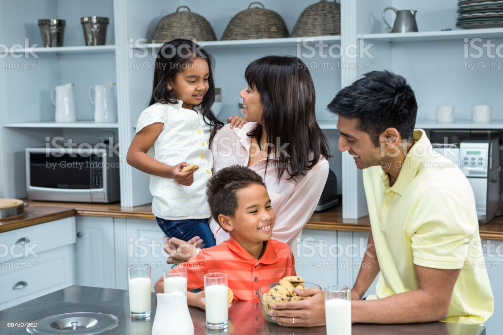 Happy family in the kitchen ready to eat biscuits foto stock royalty-free