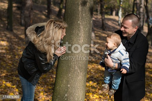 Young happy and cheerful family enjoying outdoors in a beautiful autumn day. Mother is hidding behind a tree while father and son looking to her. Autumn foliage.