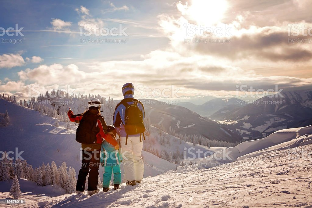Happy family in winter clothing at the ski resort stock photo