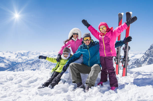 Happy family in winter holiday Laughing family in winter vacation with ski sport on snowy mountains. Happy man and woman with sons having fun and looking at camera. Family with two children enjoying winter holiday at ski resort. ski stock pictures, royalty-free photos & images