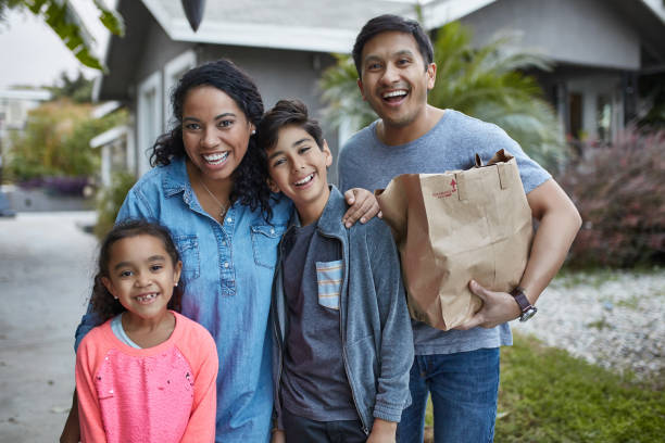 Happy family in yard after grocery shopping stock photo