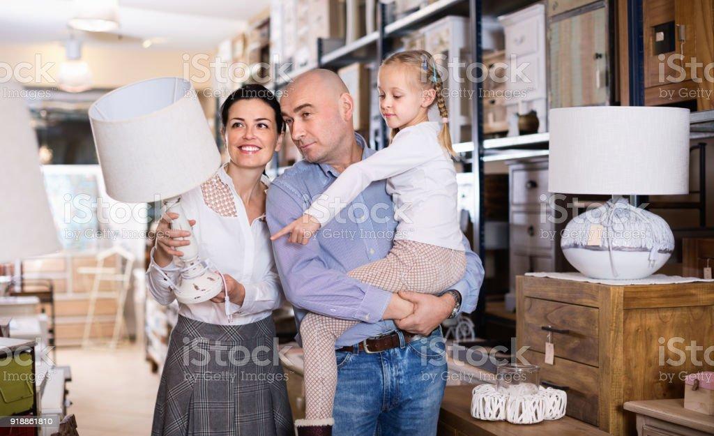 Família feliz é escolher lâmpada nova para casa na loja de móveis. - foto de acervo