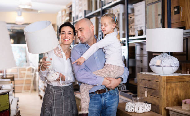 happy family is choosing new lamp for home in the furniture store. - furniture shopping stock photos and pictures