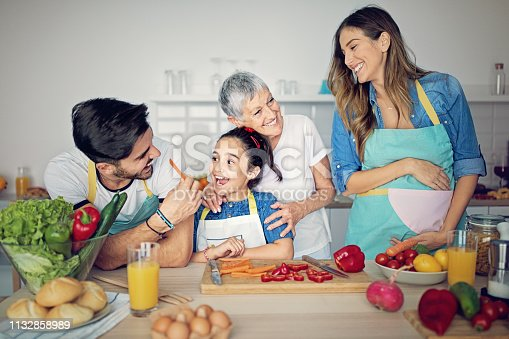 istock Happy family is cooking together in kitchen 1132858989
