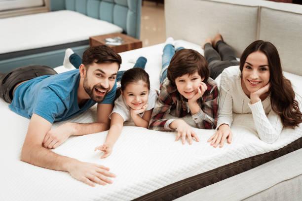 famille heureuse est reposant sur le matelas en magasin de meubles orthopédique. grande famille vérifier la souplesse du matelas - matelas photos et images de collection