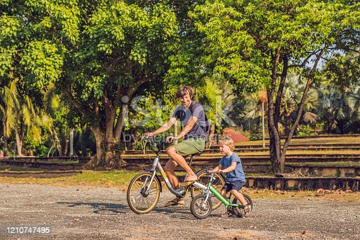 665192886 istock photo Happy family is riding bikes outdoors and smiling. Father on a bike and son on a balancebike 1210747495