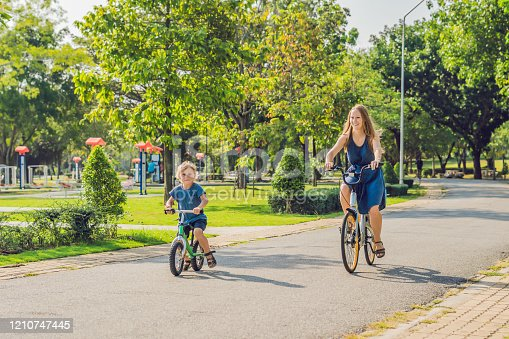 665192886 istock photo Happy family is riding bikes outdoors and smiling. Mom on a bike and son on a balancebike 1210747445