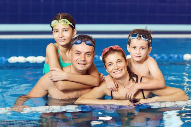 Eine glückliche Familie lächelt in einem Schwimmbad – Foto