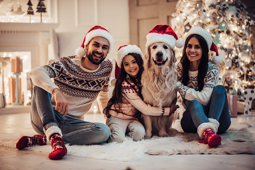 Happy Family Is Waiting For The New Year In Santa Claus Hats While Sitting Near Beautiful Christmas Tree At Home Stock Photo - Download Image Now