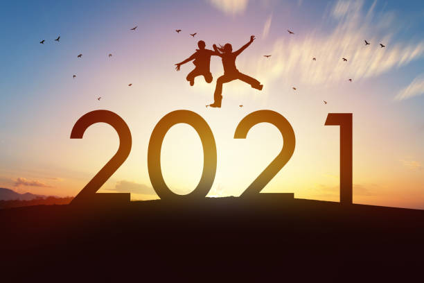 Happy family jump over 2021 with sunset background Happy boy with mother jump together over 2021 year with beautiful sunset on background. Family life of 2021 year, Happiness, Travel destination and successful concept. new years day stock pictures, royalty-free photos & images