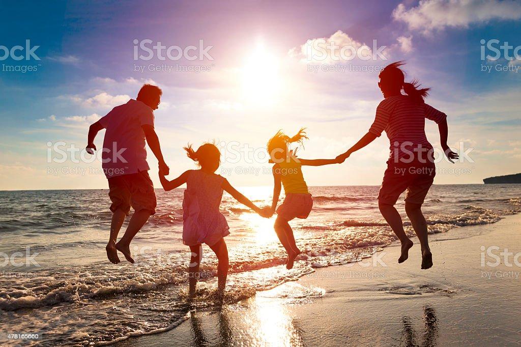 FAMIGLIA FELICE saltando insieme sulla spiaggia - foto stock