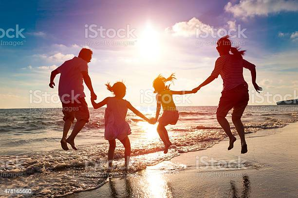 Photo of happy family jumping together on the beach