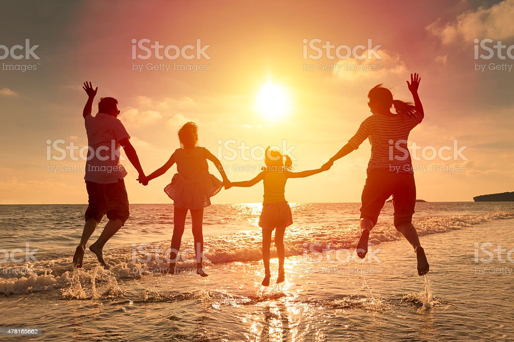 happy family jumping together on the beach stock photo