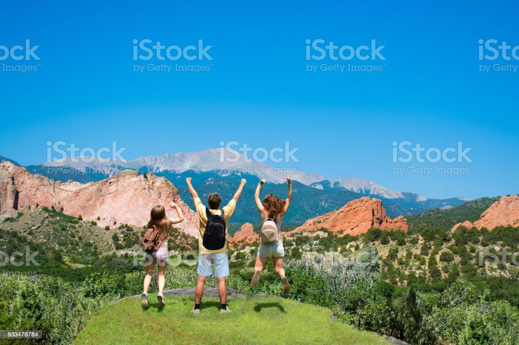 Happy family jumping with raised hands on vacation hiking trip. stock photo