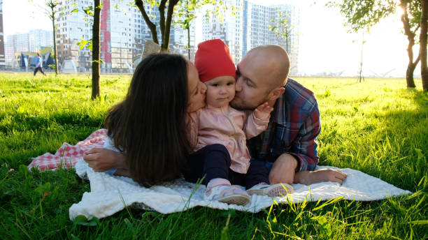 Happy family lies on grass in summer park. Parents kiss a little baby girl on the cheeks on both sides Happy family lies on grass in summer park. Parents kiss a little baby girl on the cheeks on both sides. little girl kissing dad on cheek stock pictures, royalty-free photos & images