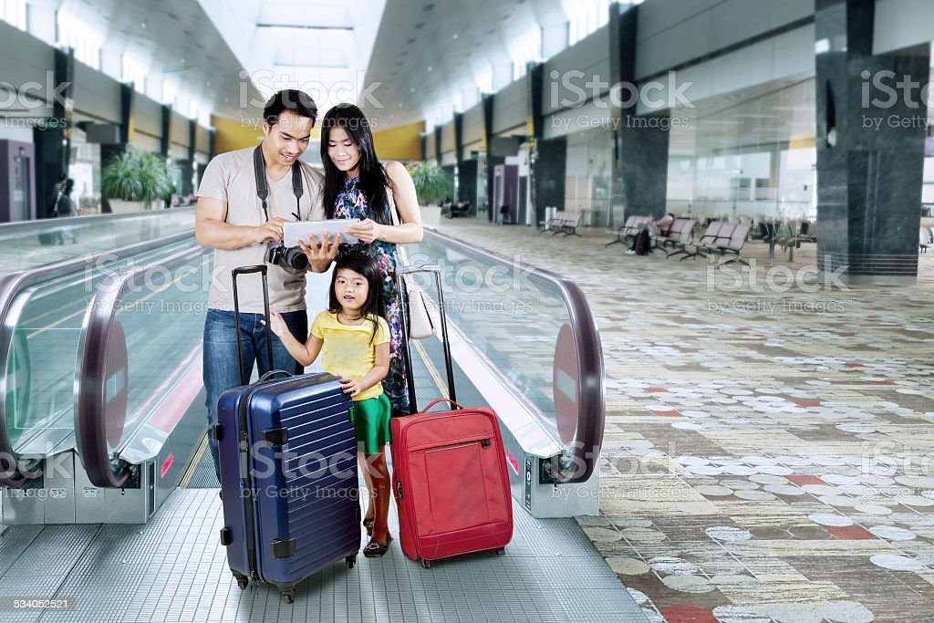 Happy family looking a map on tablet stock photo