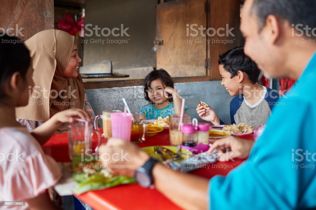 Happy family looking at girl in restaurant - Royalty-free 10-11 Years Stock Photo