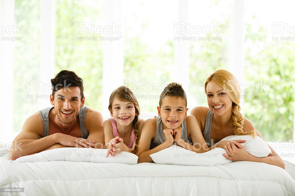 Happy family lying down on bed foto royalty-free