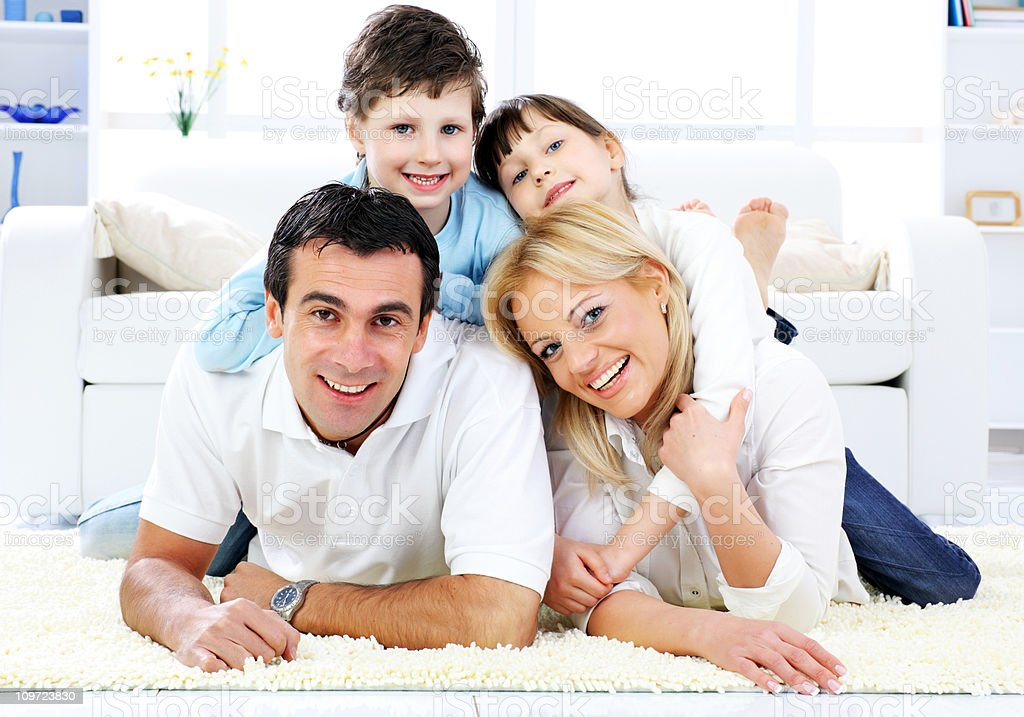 Happy family lying down on the carpet. royalty-free stock photo