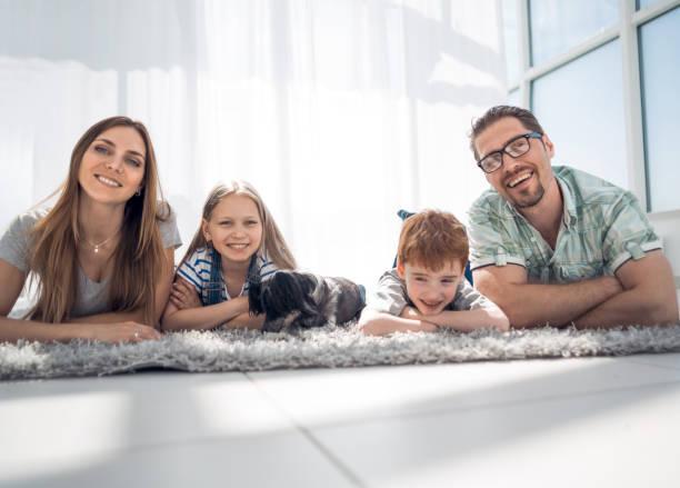 família feliz, deitado no tapete no quarto em casa de novo - cachorro desenho - fotografias e filmes do acervo