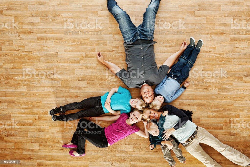 Happy family lying on floor stock photo