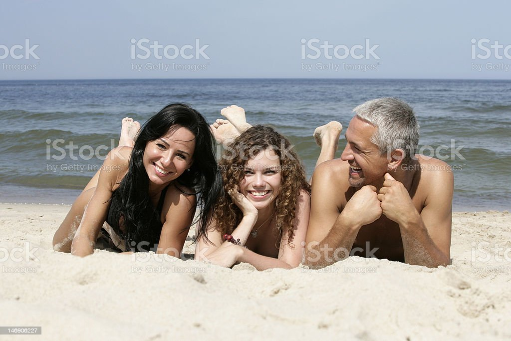 Happy family lying on sandy beach royalty-free stock photo