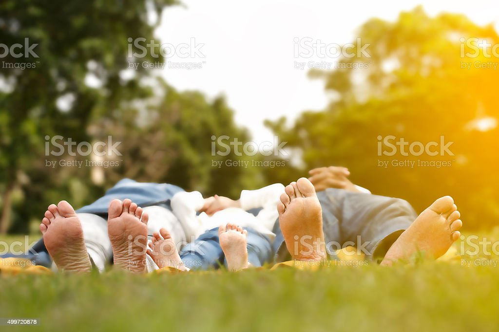 Happy family lying  outdoors together barefoot stock photo