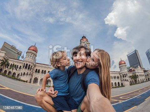 happy family makes selfie on background of Merdeka square and Sultan Abdul Samad Building. Traveling with children concept.