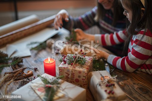 Happy mother and daughter wrapping Christmas presents at home.
