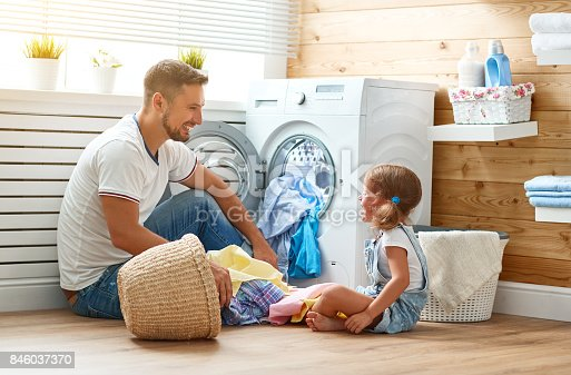 istock Happy family man father householder and child   in laundry with washing machine 846037370