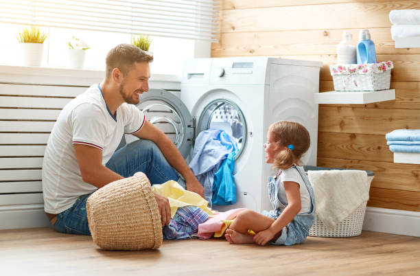 Happy family man father householder and child   in laundry with washing machine stock photo