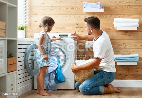 istock Happy family man father householder and child   in laundry with washing machine 846037600
